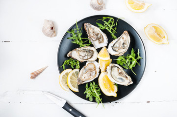 Fototapeten Schalentier Oysters with lemon fruit on a black plate on a white wood table