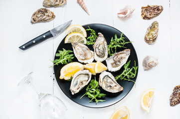 Oysters with lemon fruit on a black plate and glass of wine on a white wood table.