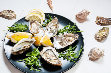 Oysters with lemon fruit on a black plate on a white wood table.