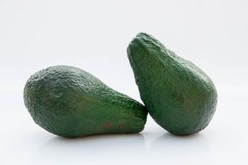 due avocado verdi su fondo bianco