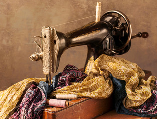 Old sewing machine, fabric and sewing thread in vintage style.