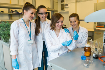 Group of attractive girls doing experiments in a professional laboratory