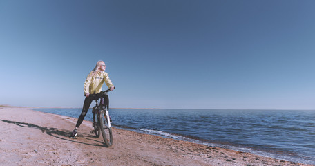 A girl on a bicycle by the sea