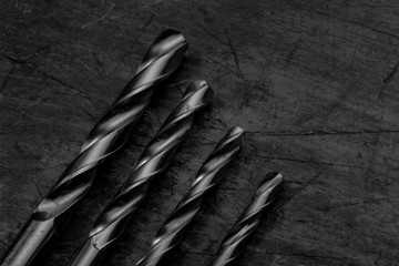 Set of drill bits on wooden background. Symbolic repair tool, black and white