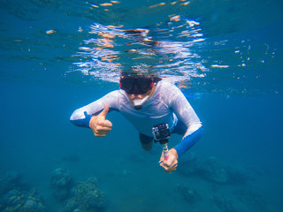 Young sportsman in snorkeling mask shows thumb underwater.