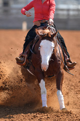 A front view of a rider sliding the horse in the dirt