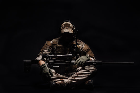 Portrait soldier or private military contractor holding sniper rifle. war, army, weapon, technology and people concept. Image on a black background.