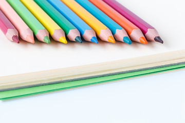 closeup image of color pencils on the book and white background