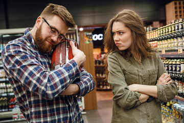 Man holding keg of beer with displeased woman