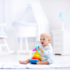 Wall Mural - Baby playing with toy pyramid. Kids play