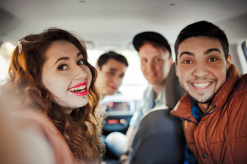A company of four friends makes selfie inside the car