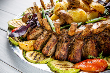 Meat plate with delicious pieces of meat, salad, ribs, grilled vegetables and potatoes on white wooden table