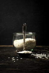 Raw Arborio rice on spoon and in jar on black background