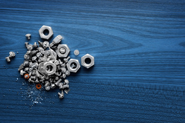 Nuts, screws and bolts on wooden blue working desk
