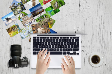 Photographer editing photos on laptop surrounded with pictures, coffee cup and camera
