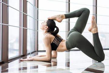 Young woman doing yoga asana Eka Pada Rajakapotasana against window in gym