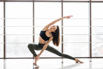Beautiful woman practices yoga asana Anjaneyasana in studio