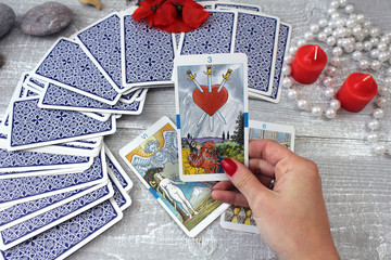 Tarot cards, candles and accessories on a wooden table
