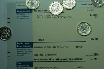 Personal income statement showing income and tax figures  for UK tax return covered by some new one pound coins