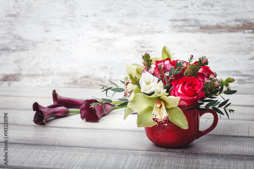 Small Red Vase With Bouquet Of Flowers And Lilies On Wooden Table