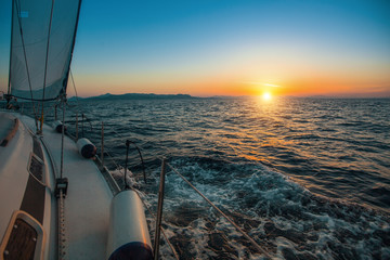 Wall Mural - Sailboat with sails set to Sea at full speed at amazing sunset. Luxury cruise yacht.  .