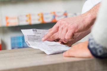 Apotheker erklärt einem Kunden einen Beipackzettel
