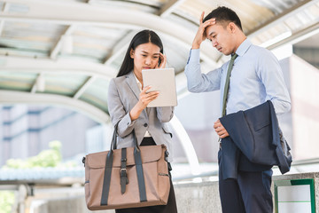 Two stressed Asian businessman and woman outdoor with tablet.