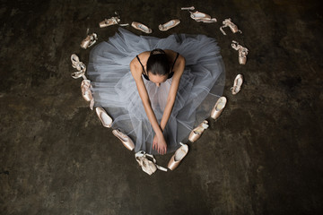 Ballerina with crossed hands sitting inside heart made of pointe shoes