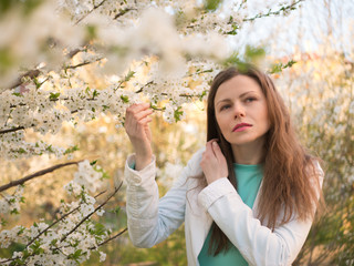 outdoor portrait of a beautiful woman in white jacket among white blossom tree