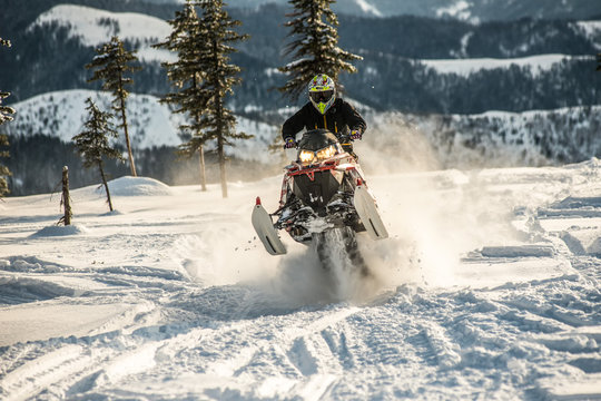 Rider on the snowmobile in the mountains. active drive