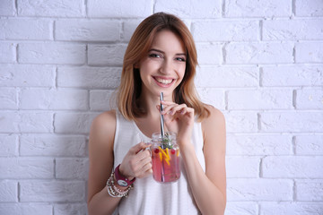 Beautiful young woman with lemonade near light brick wall