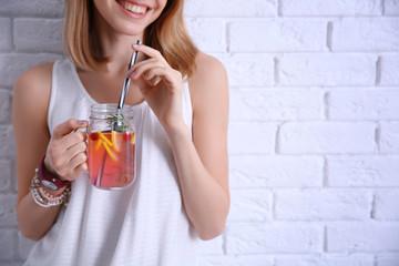 Young woman with lemonade near light brick wall