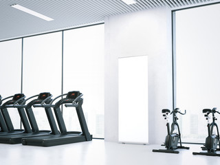 Treadmills, bicycle simulators and blank roll-up bunner. 3d rendering