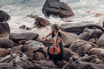 beautiful young woman playing cello on stone beach at stormy weather