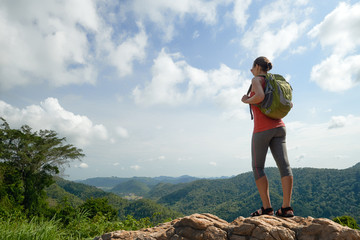 Traveller woman with backpack enjoying  view to valley on background mountains