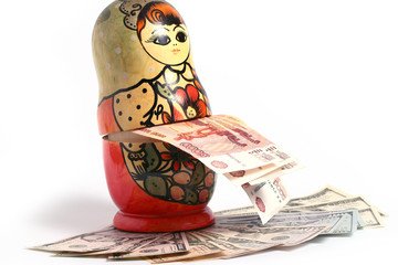 Russian national wooden toy with paper bills standing on a pile of American dollars
