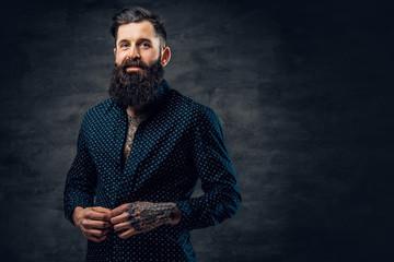 Bearded tattooed male dressed in dark blue jacket.