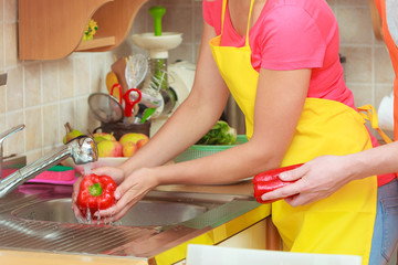 Couple washing fresh vegetables in kitchen