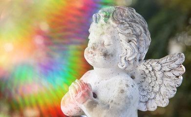 praying stone angel with colorful sunbeam