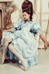 Indoors shot in the Marie Antoinette style. A young luxurious girl in a lush blue retro dress with a high hairstyle sits in a chair. Woman tired of luxury