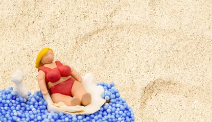 Handmade doll in beach scene. Tourist woman with fat body in red bikini.