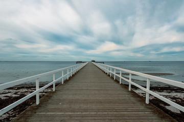 Empty wooden pier walkway on sea shore