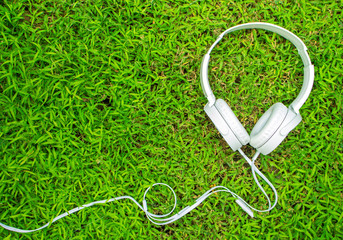 White headphones on green grass. Summer lawn with personal device.