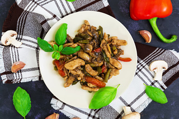 Stir Fry Chicken with peppers and peas on dark background. Top view
