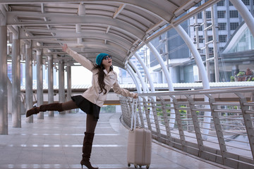Asian Travel woman smiling and happy to wearing sweater coat, blue yarn hat with luggage, walking on shopping business street background for traveler vacation tourist concept