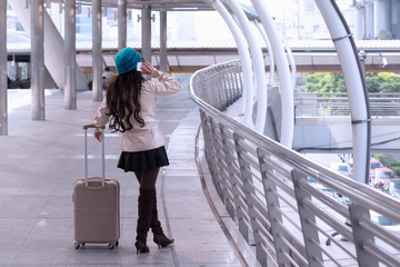 Asian Travel woman wearing sweater coat, blue yarn hat with luggage, calling phone at shopping business street background for traveler vacation tourist concept