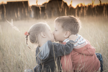 Children sitting in field at sunset and kiss