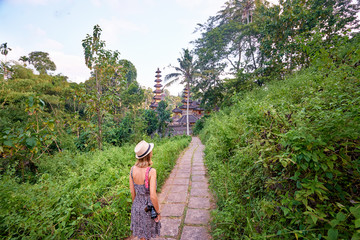 Tourism and travel. Young woman in hat with camera walking on path to Balinese temple.