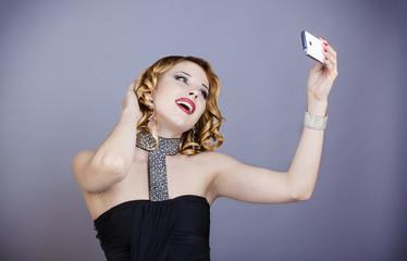 Jeune femme souriante en tenu de soirée, prend un selfie avec son téléphone portable