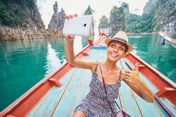 Happy vacation in Thailand. Pretty young woman taking selfie on smartphone sailing Khao Sok National Park lake on traditional longtail boat.